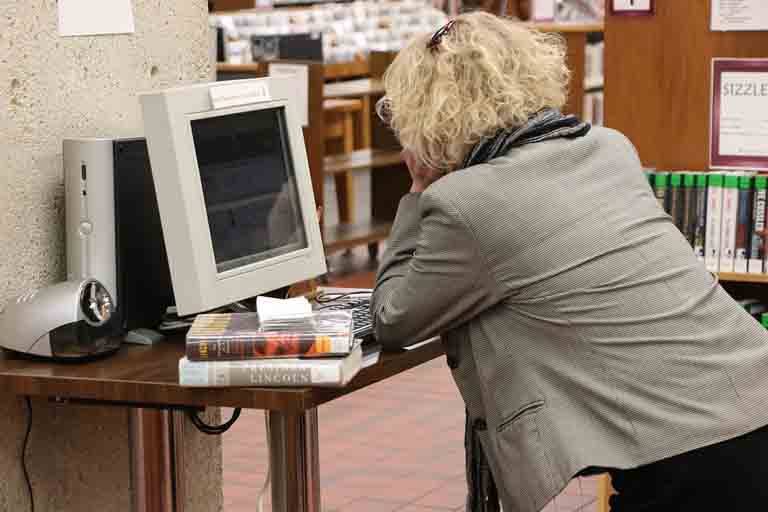 a lady looking through the relational database of a library